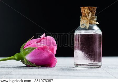 Pink Rose Flower And Glass Of Bottle Essential Oil Or Rose Water With Rose Petals, Spa And Aromather