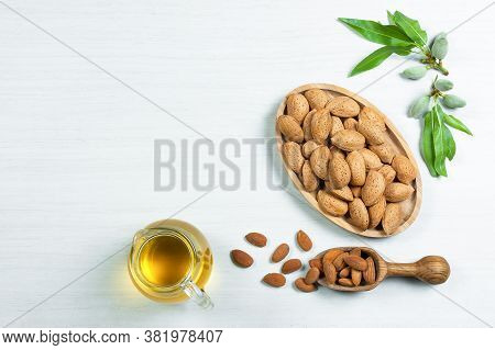 Glass Bottle Of Almond Oil And Almond Nuts, Almonds With Shell In Bamboo Bowl On Rustic Backdrop Wit