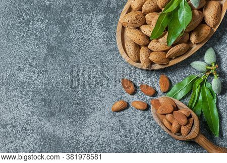 Almond Nuts In Wooden Shovel, Almonds With Shell In Bamboo Bowl On Wooden Background With Green Fres