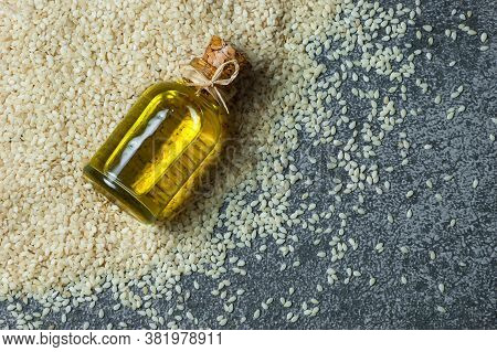 Glass Bottle Of Sesame Oil And Raw Sesame Seeds On Grey Rustic Table. Uncooked Sesame Background Con