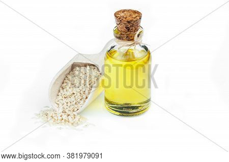 Glass Bottle Of Sesame Oil And Raw Sesame Seeds In Wooden Shovel Isolated On White Background. Uncoo