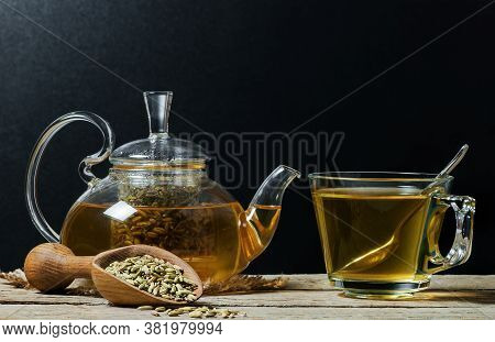 Herbal Infusion Fennel Tea In Glass Tea Pot With Dried Fennel Seeds In Wooden Shovel On  Rustic Tabl