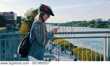 Young Caucasian Sporty Woman Rolling Rollerblades Over The Bridge While Using Smartphone. . High Qua