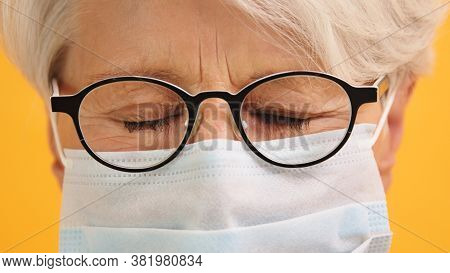 Close Up Shot Of Sad Old Woman With Glasses Over Closed Eyes And Medical Mask. Protect Vulnerable Pe