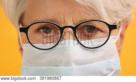 Close Up Shot Of Sad Old Woman With Glasses And Medical Mask. Protect Vulnerable People. High Qualit