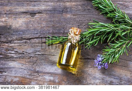 Top View Bottle Glass Of Essential Rosemary Oil With Rosemary Branch And Flower On Wooden Rustic Bac