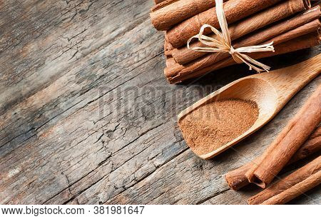 Close Up Cinnamon Sticks And Cinnamon Powder In Wooden Spoon On Wooden Table Background, Healthy Spi