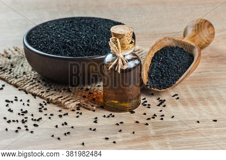 Black Cumin Seeds Essential Oil , Nigella Sativa In Glass Bottle, Black Cumin In Bowl And Wooden Sho