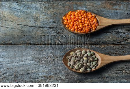Red And Green Lentils In Wooden Spoon On Wooden Background. Uncooked Lentil Legumes, Herbaceous Plan