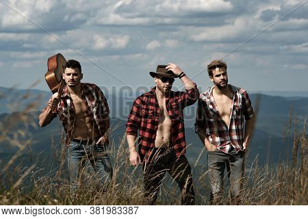 Handsome Men Walking In The Mountains. Group Of People Man Hiking Through Countryside. Three Young M