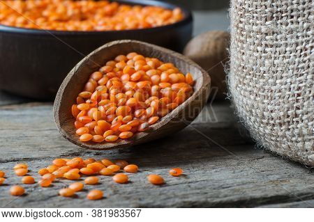 Red Lentils In Wooden Spoon On Wooden Background. Uncooked Red Lentil Legumes, Herbaceous Plant (len