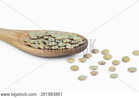 Green Lentils In Wooden Spoon Isolated On White Background. Uncooked Lentil Legumes, Herbaceous Plan