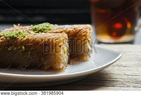 Turkish Famous Dessert Burma Kadayif On Plate With Pistachio Nuts Near Glass Of Turkish Tea, Shredde