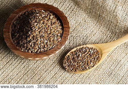 Heap Of Flax Seeds Or Linseeds In Spoon And Bowl On Wooden Or Burlap Sack Backdrop. Flaxseed Or Lins