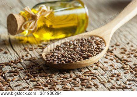 Heap Of Flax Seeds Or Linseeds In Spoon And Bowl With Glass Of Linseed Oil On Wooden Backdrop. Flaxs