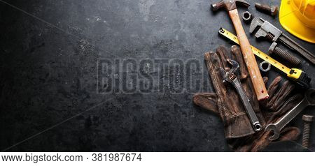 Hardhat, hammer, wrench, gloves, and other worn and dirty tools on dark background with copy space. Father's day, DIY, home improvement, or labor day background concept.