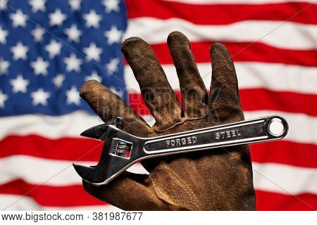 Old worn work glove holding adjustable wrench with Forged Steel text. Strong American workforce or industry, or America labor concept.