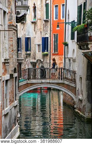 Houses Along Narrow Canal Connected By A Stone Bridge In Venice, Italy. Venice Is Situated Across A