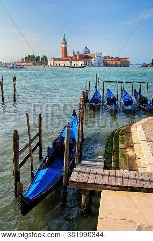 Gondolas Moored Near San Marco Square Across From San Giorgio Maggiore Island In Venice, Italy. Gond