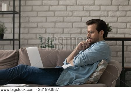 Pensive Caucasian Man Work On Laptop At Home Thinking