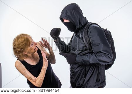 Protester With Face Mask And Back Pack Threatens Small Senior Woman