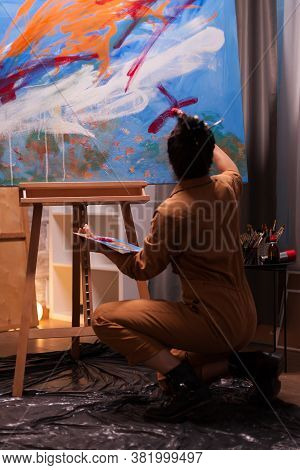 Back View Of Artist In Art Studio Working On Impressionism Painting. Modern Artwork Paint On Canvas,
