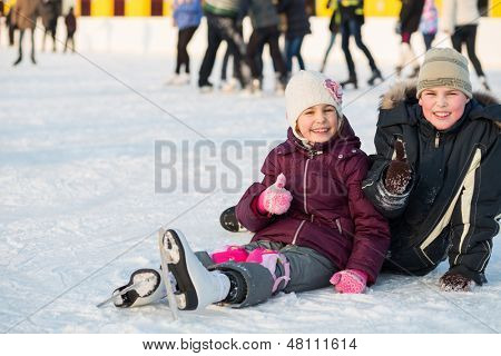 Brother and sister together fell while skating and doing a thumbs up