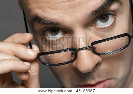 Closeup portrait of a businessman with hand on glasses making a face against gray background