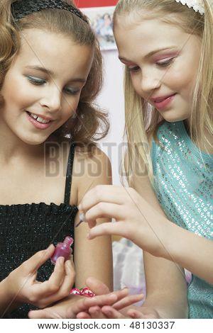 Closeup of a young girl applying nail polish to friend's fingernails