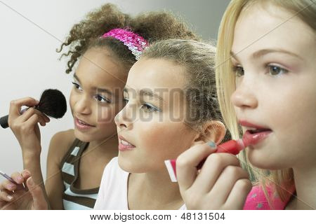 Closeup side view of three girls side by side putting on makeup and lipgloss