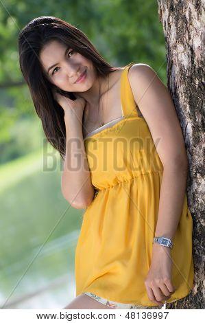 Feliz mujer tailandesa posando sobre un fondo de árboles