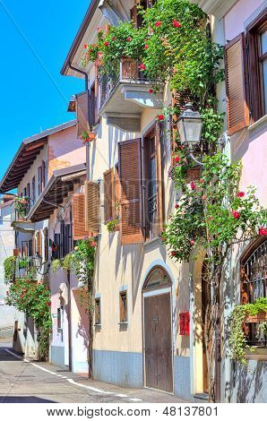 Vertical oriented image of typical italian house with balcony and blinds decorated with flowers in town of La Morra in Piedmont, Northern Italy.