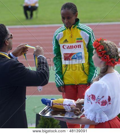 DONETSK, UKRAINE - JULY 11: IAAF Ambassador Ato Boldon hand over silver medal for 3000 m race to Berhan Demiesa, Ethiopia during 8th IAAF World Youth Championships in Donetsk, Ukraine on July 11, 2013