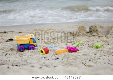 Children's toy on the beach, by the sea.