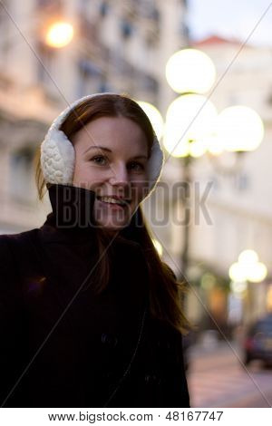 Woman With Ear Muffs Smiling In The Evening Light