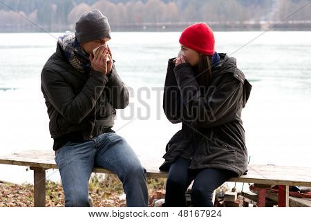 A Young Couple Next To Each Other Blowing Their Noses