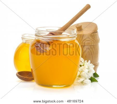glass jar full of honey and stick isolated on white background