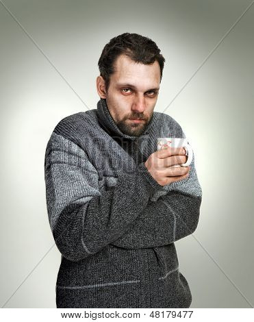 Cold, sick man dressed in grey sweater holding a cup of tea in hands isolated on grey background loo