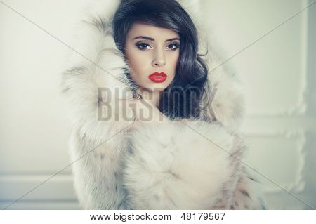 Fashion photo of beautiful young lady in a luxurious fur coat