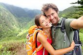 Hiking couple - Active young couple in love. Couple taking self-portrait picture on hike. Man and woman hiker trekking on Waihee ridge trail, Maui, USA. Happy romantic interracial couple. poster
