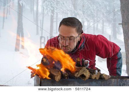 Man Fanning Fire In Grill