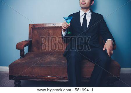 Businessman On Vintage Sofa Drinking Cocktail