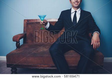 Happy Businessman On Sofa Drinking Cocktail