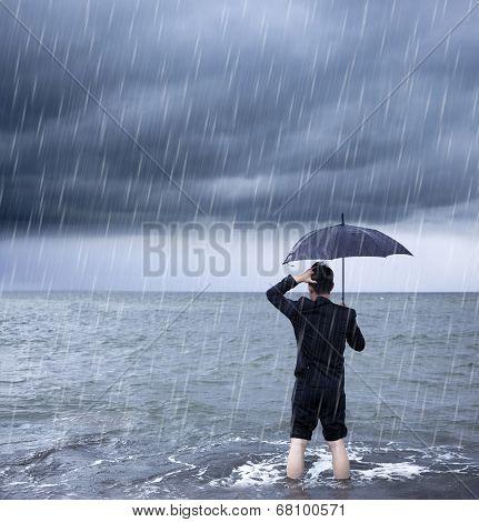 Upset Business Man Holding A Umbrella With Cloudburst Background