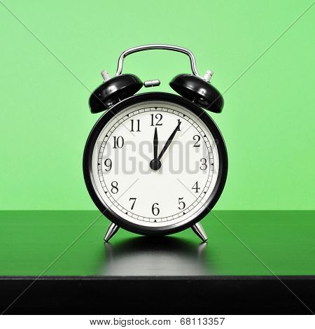a mechanical alarm clock on a bedside table