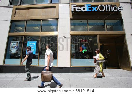 NEW YORK CITY - FRIDAY, JUNE 20, 2014:   Pedestrians walk past a FedEx Office store in New York City on Friday, June 20, 2014.