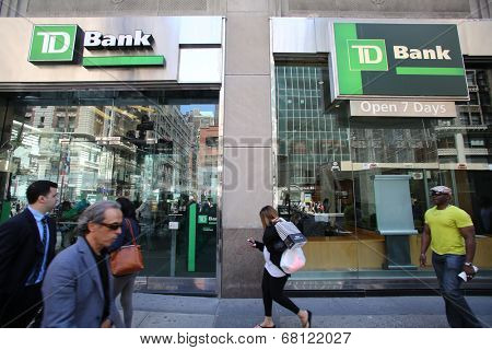 NEW YORK CITY - FRIDAY, JUNE 20, 2014:   Pedestrians walk past TD Bank, N.A. in New York City on Friday, June 20, 2014. TD or Toronto Dominion is a major savings bank.