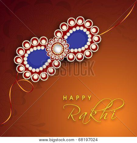 Beautiful rakhi on shiny brown background for occasion of Happy Raksha Bandhan celebrations.