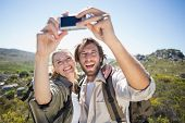 Hiking couple standing on mountain terrain taking a selfie on a sunny day poster