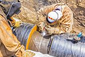 Welders welding pipeline together in a teamwork poster